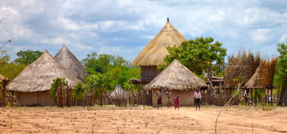 Children standing outside Tonga villiage of thatched mud huts, near Binga, Zimbabwe